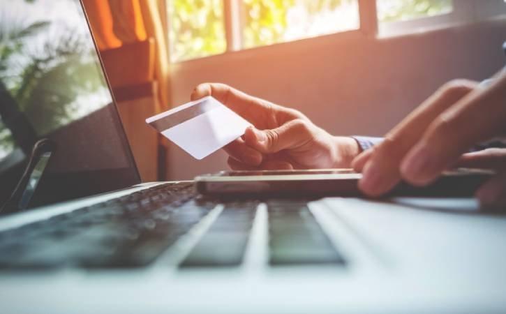 Homem segura cartão de crédito em frente ao computador